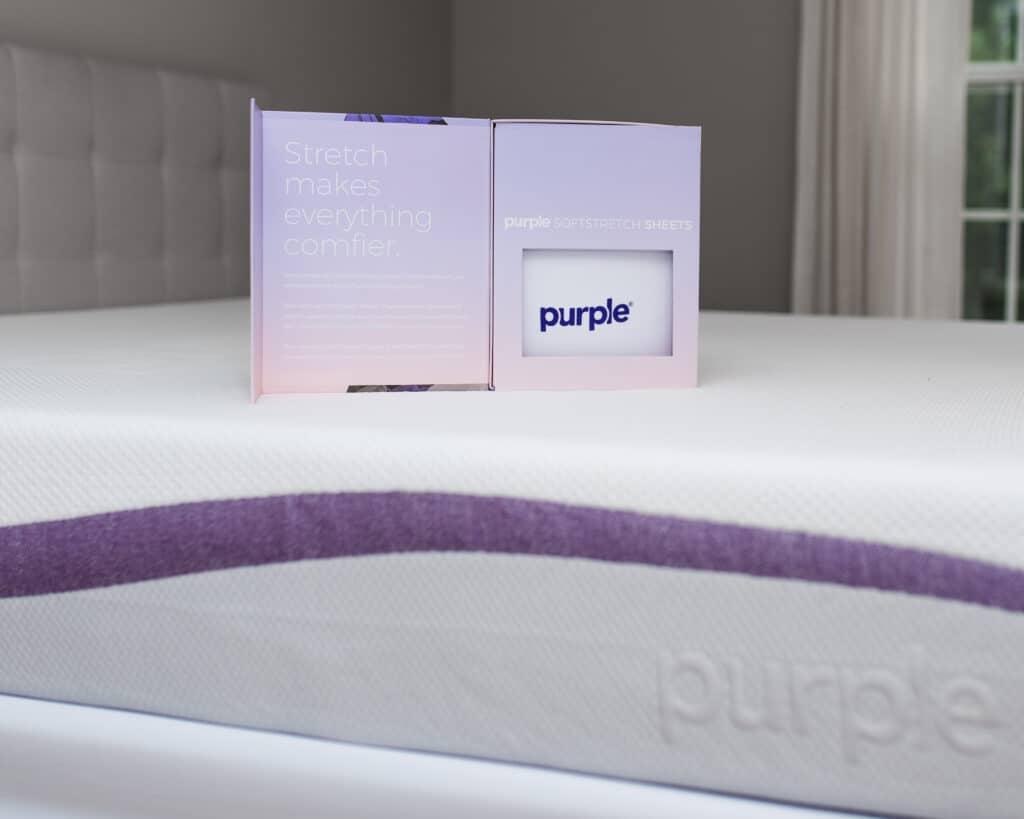 Box of sheets on Purple mattress