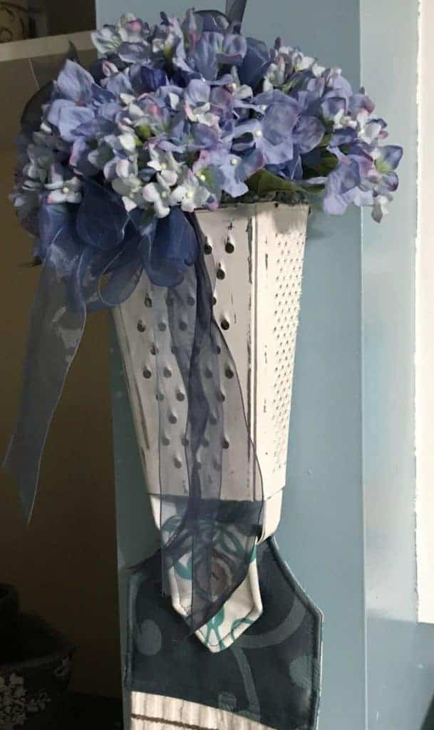 cheese grater repurposed as a farmhouse vase and towel holder