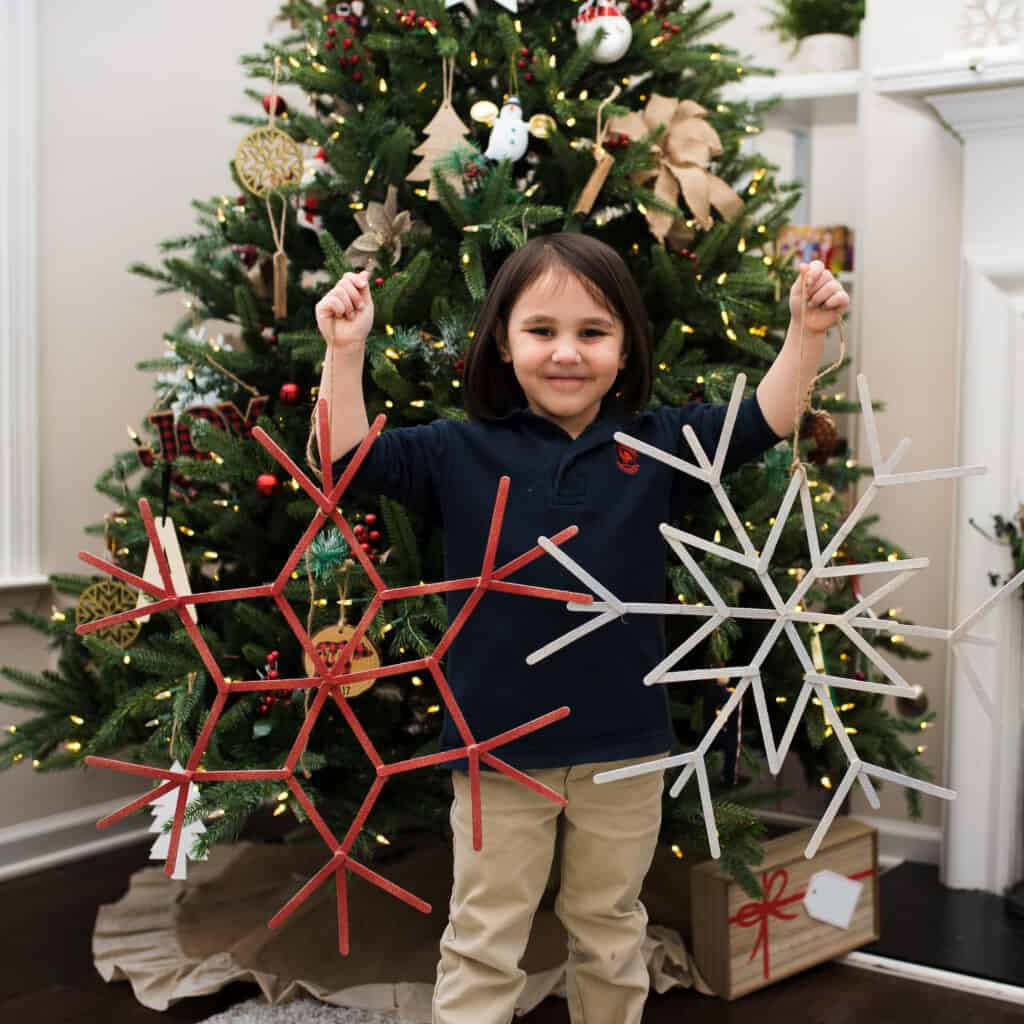 Aren holding snowflake wreaths in front of Christmas tree