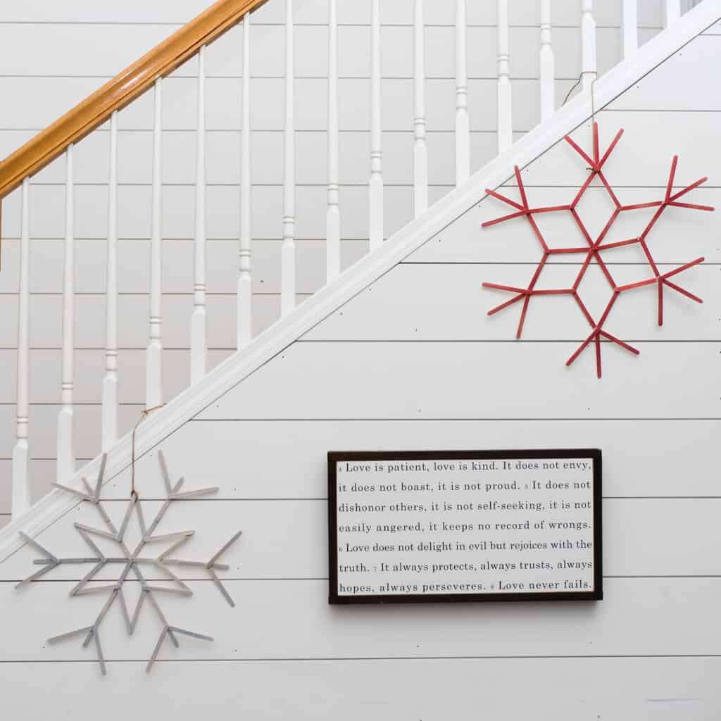 DIY craft stick snowflake wreaths hanging on shiplap wall