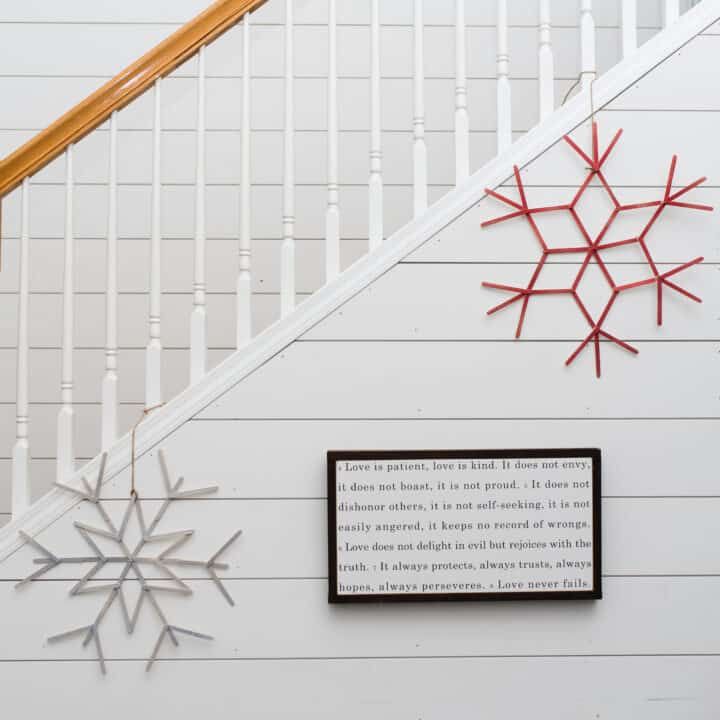 DIY craft stick snowflake wreaths hanging on shiplap wall