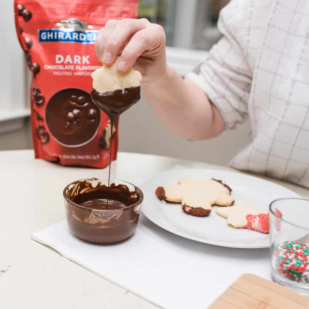 dipping sugar cookie into Ghirardelli melted chocolate