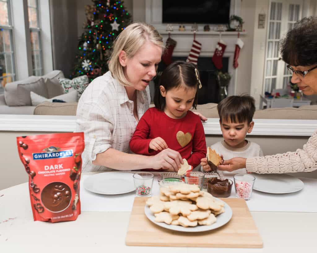 kids decorating cookies with grandma and mom
