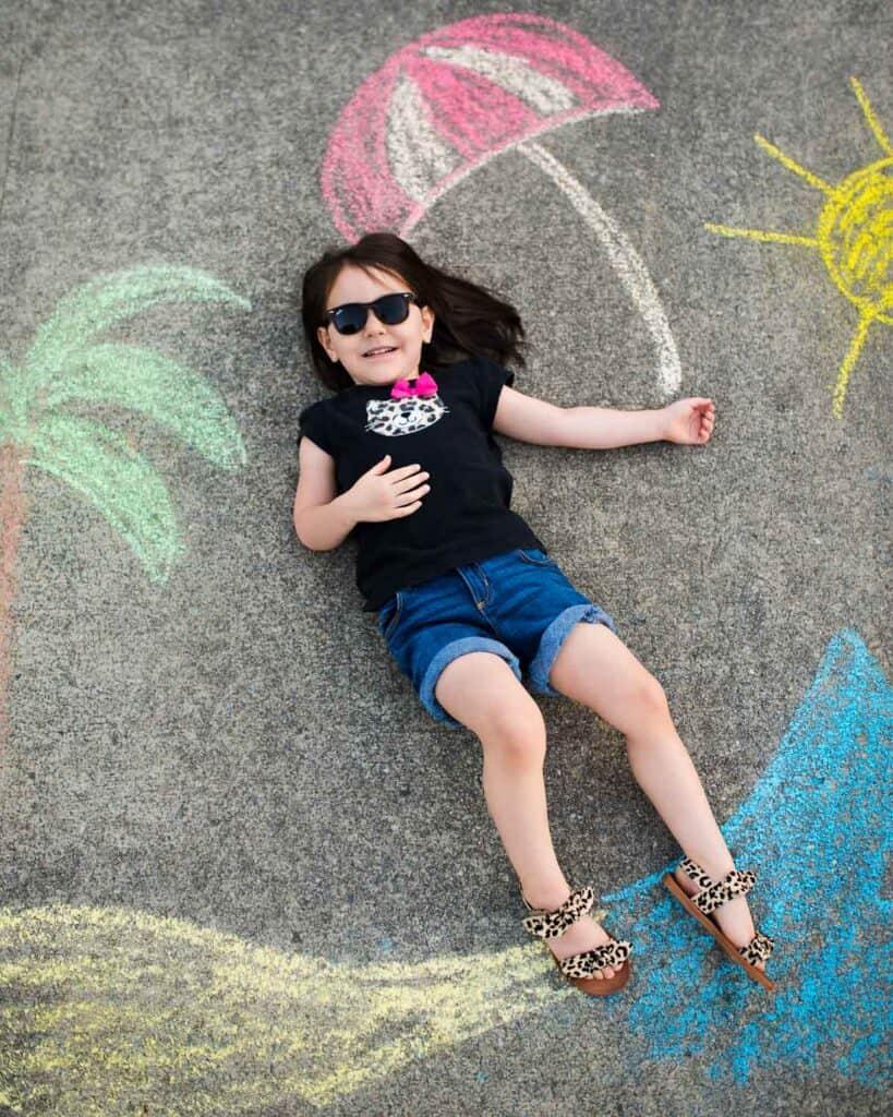 little girl lying on sidewalk surrounded by sidewalk chalk beach scene mural