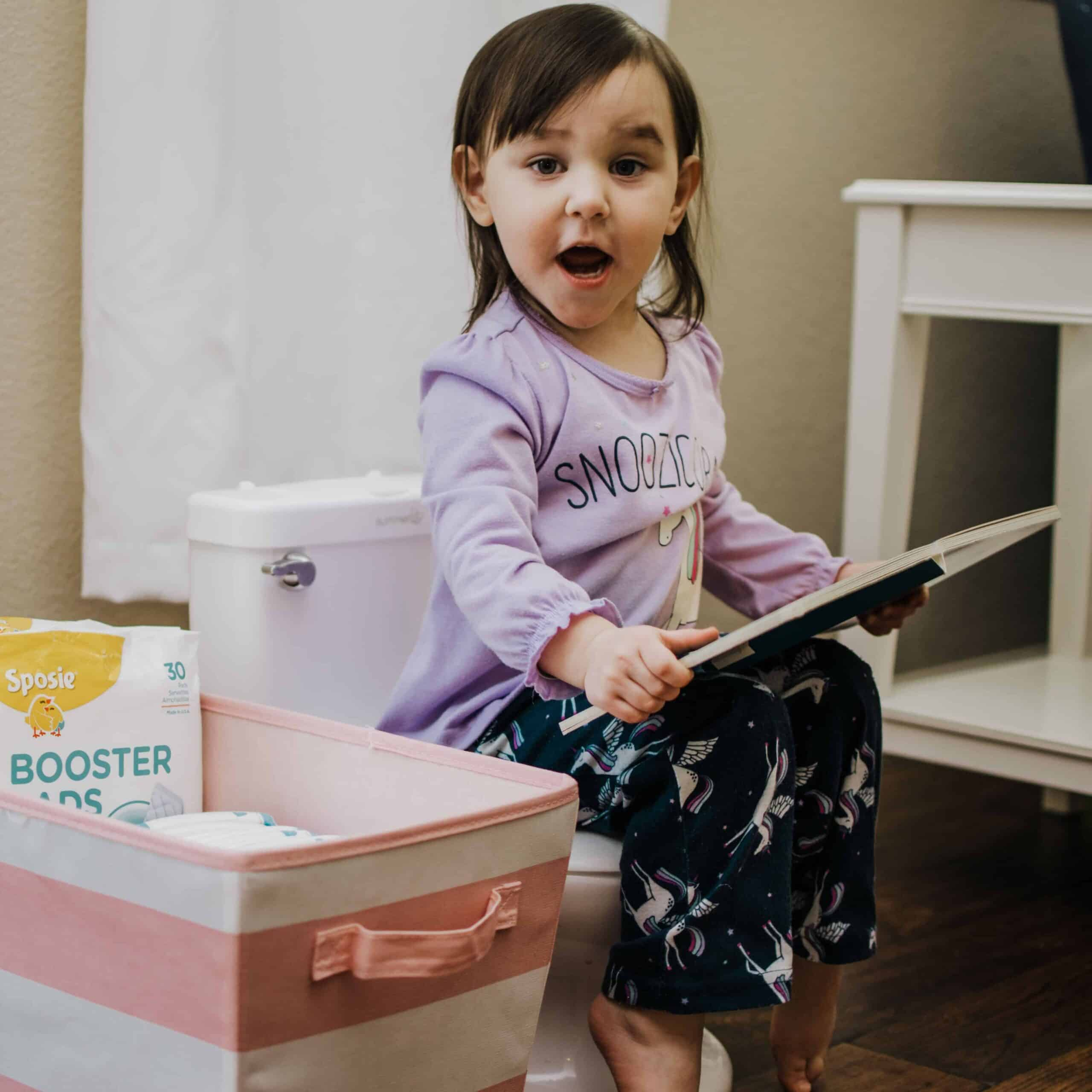 2 year old girl reading a book while potty training