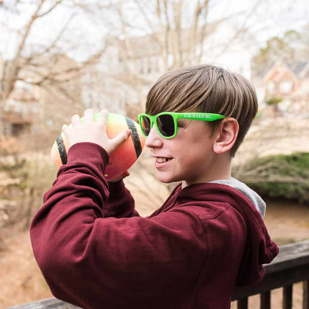 action for healthy kids sunglasses with boy playing football