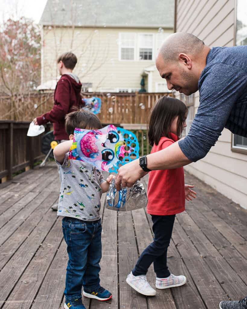 family playing outside with zuru bubble gloves
