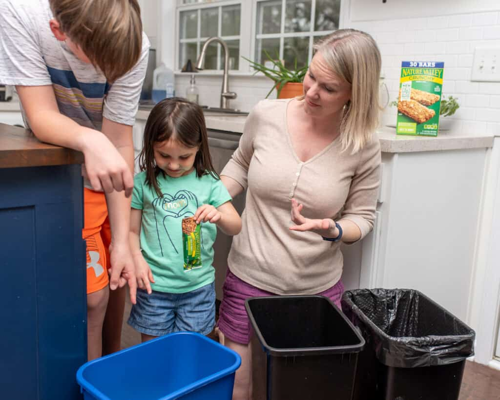 family sorting recycling into bins